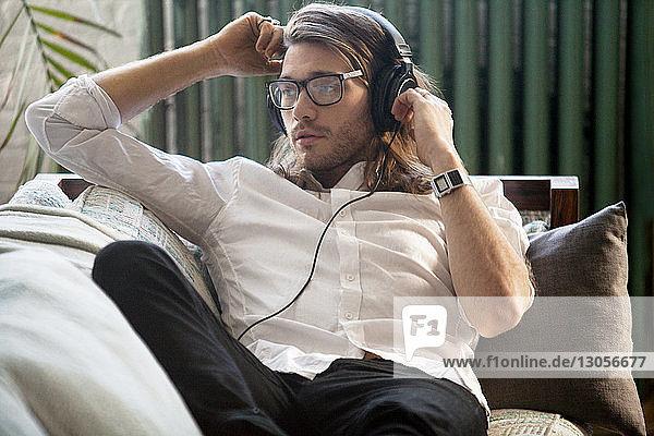 Mann schaut weg  während er zu Hause Musik hört
