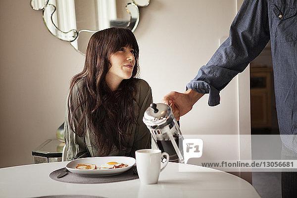 Ausgeschnittenes Bild eines Mannes  der seiner Freundin zu Hause Kaffee in die Tasse gießt