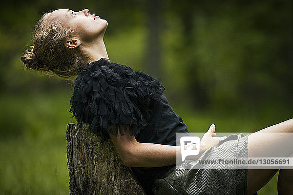 Side view of woman leaning on tree stump