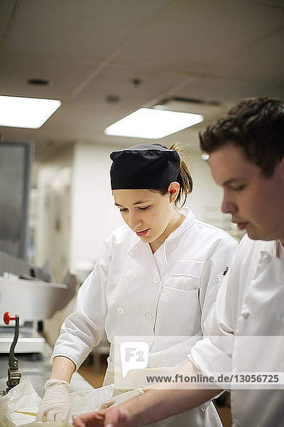 Male and female chef preparing food in commercial kitchen