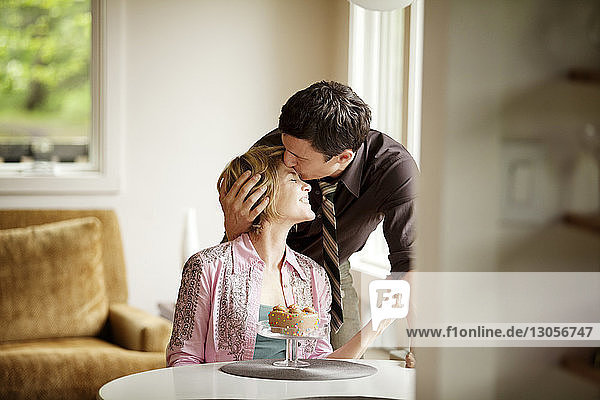 Mann küsst Frau zu Hause auf die Stirn