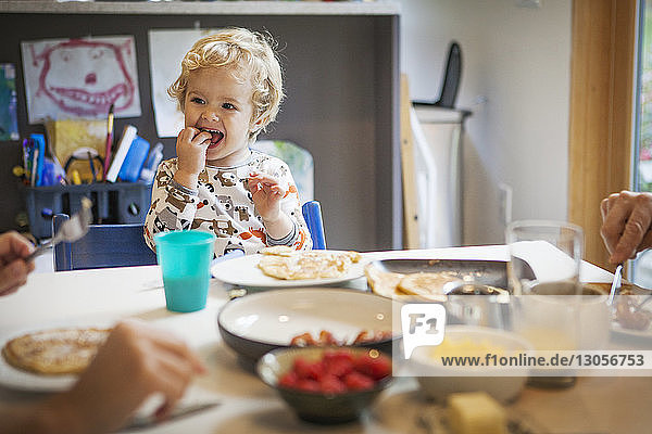 Happy boy eating breakfast at table in home