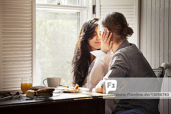 Affectionate couple by breakfast table at home