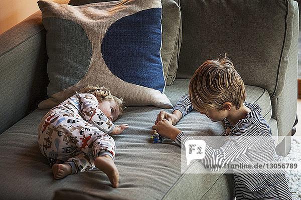 Geschwister spielen zu Hause auf dem Sofa