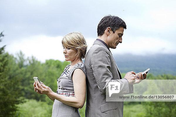 Seitenansicht eines Paares  das ein Mobiltelefon benutzt  während es gegen den Himmel steht