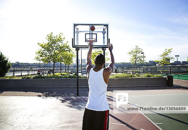 Rear view of sportsman throwing basketball in hoop on sunny day