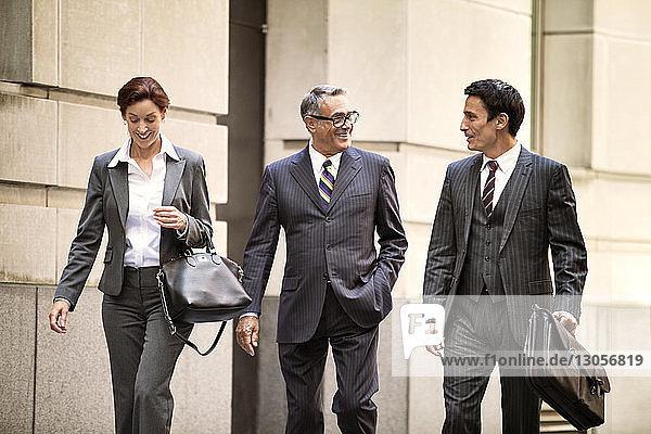 Happy business people walking on city street