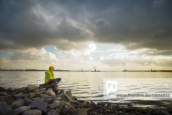 Woman sitting on rocks by lake against cloudy sky