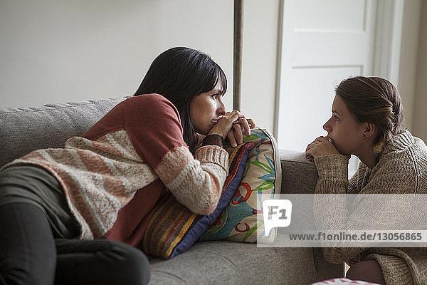 Tochter sieht Mutter an  die sich zu Hause auf dem Sofa entspannt