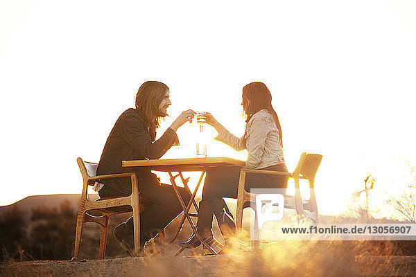 Couple toasting wine glasses while sitting on chairs at field
