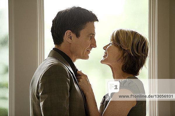 Glückliche Frau justiert Krawatte  während sie den Mann zu Hause anschaut