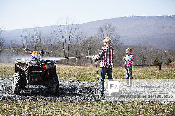 Brother looking at boy washing quadbike on field