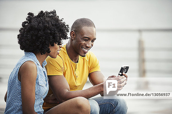 Couple looking at mobile phone while sitting on promenade