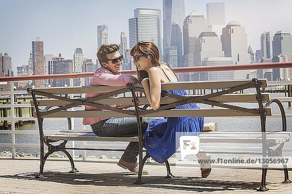 Glückliches Paar sitzt auf der Bank am Geländer