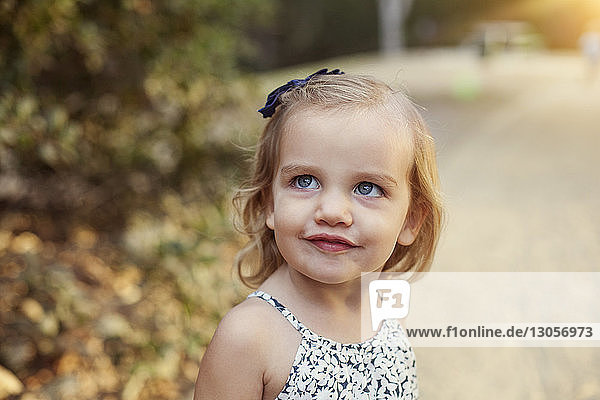 Close-up of cute girl looking away on footpath