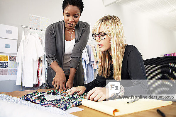 Modedesignerinnen prüfen Stoffe und diskutieren am Schreibtisch in einem Workshop