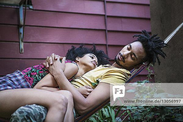 Frau betrachtet Mann  der auf Hängematte im Rasen schläft