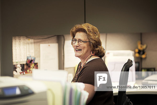 Smiling woman looking away while sitting in office