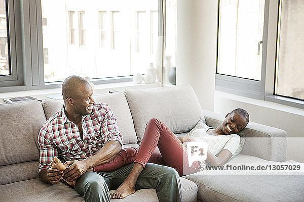 Glückliches Paar genießt zu Hause auf dem Sofa