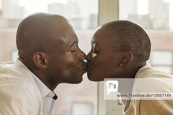 Close-up of couple kissing by window