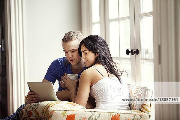 Glückliches Paar benutzt Tablet-Computer  während es zu Hause auf einem Sessel sitzt