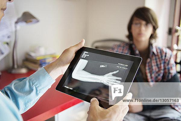 Ausschnitt eines Arztes  der die Hand röntgt  mit einem im Hintergrund sitzenden Jungen