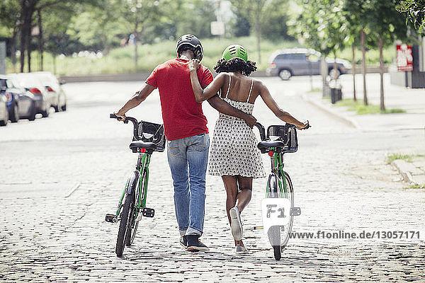 Rückansicht eines Paares mit dem Arm um den Arm auf einer Straße in der Stadt
