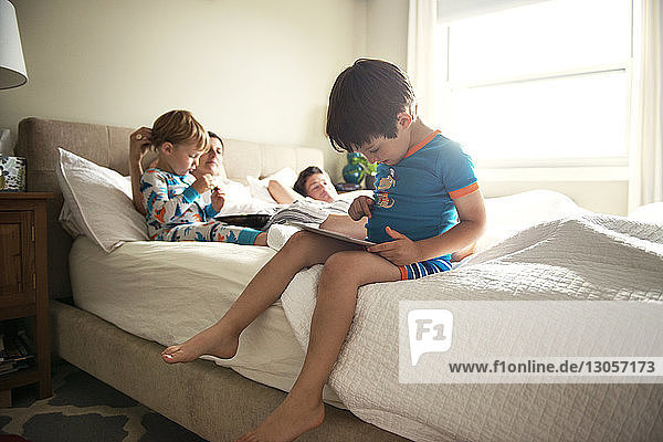 Boy using tablet computer while family lying on bed at home