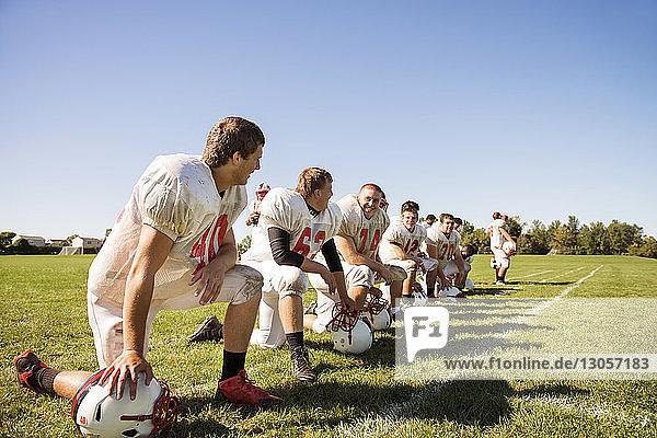 Happy football team kneeling on grassy field against sky