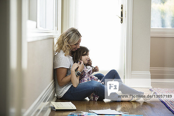 Mother and daughter sitting on floor at home