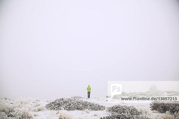 Fernansicht eines Wanderers  der auf einem schneebedeckten Feld läuft