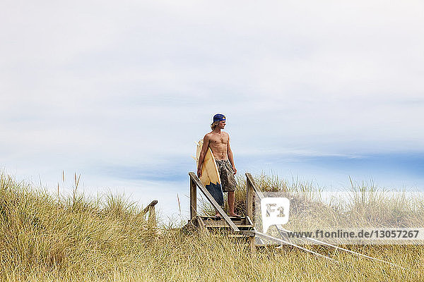Man looking away while standing on steps with surfboard against sky