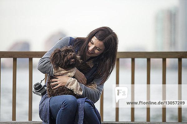 Frau sieht Hund an  während sie auf Bank am Hudson River sitzt