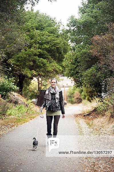 Porträt einer Frau mit Hund beim Spaziergang auf der Straße