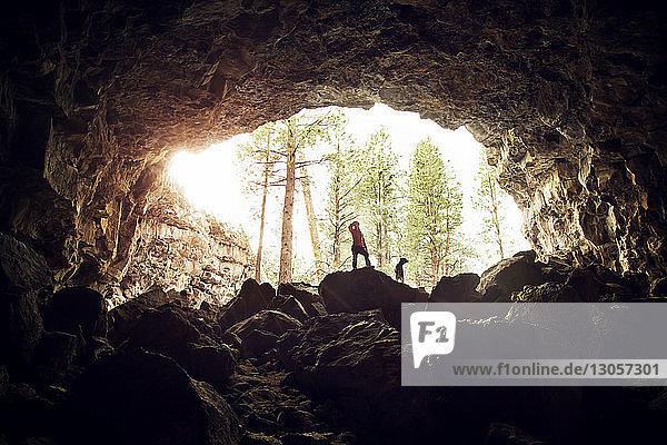 Frau steht mit Hund auf Felsen in Höhle