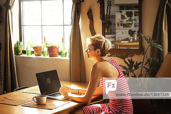 Frau mit Laptop-Computer schaut weg  während sie zu Hause am Tisch sitzt