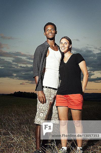 Porträt eines glücklichen jungen Paares auf dem Spielfeld stehend