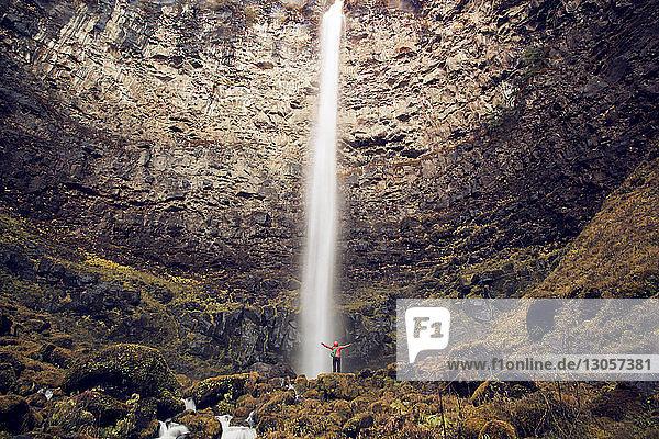 Fernansicht eines Wanderers  der im Wald vor einem Wasserfall steht