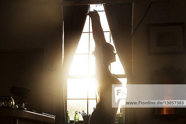 Seitenansicht einer Frau  die sich streckt  während sie zu Hause am Fenster steht
