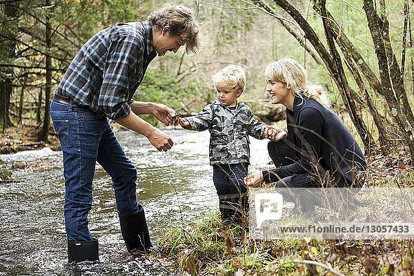Glückliche Familie betrachtet Skorpion am Fluss