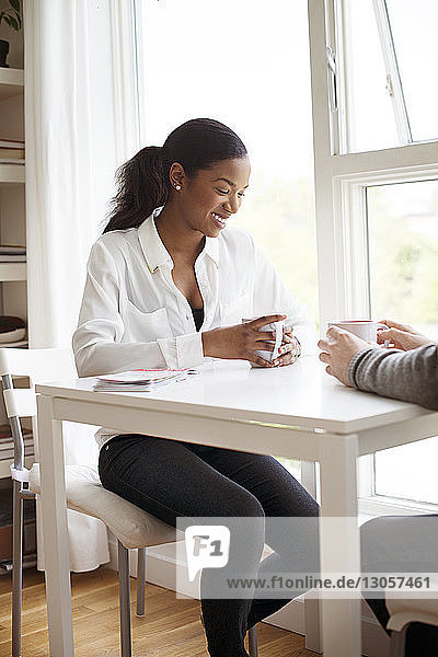 Businesswoman having coffee with male colleague at table
