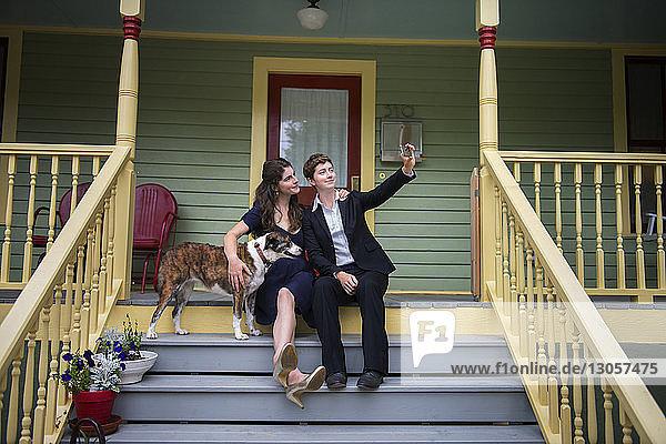Hündinnen mit Hund  die sich per Mobiltelefon selbstständig machen  während sie auf der Treppe auf der Veranda sitzen