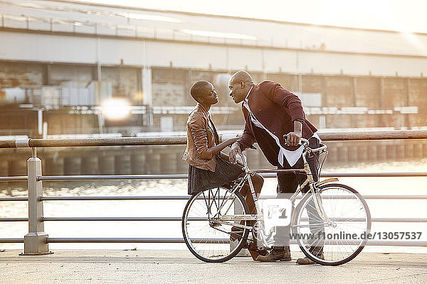 Full length of man looking at woman sitting on bicycle by railing against river