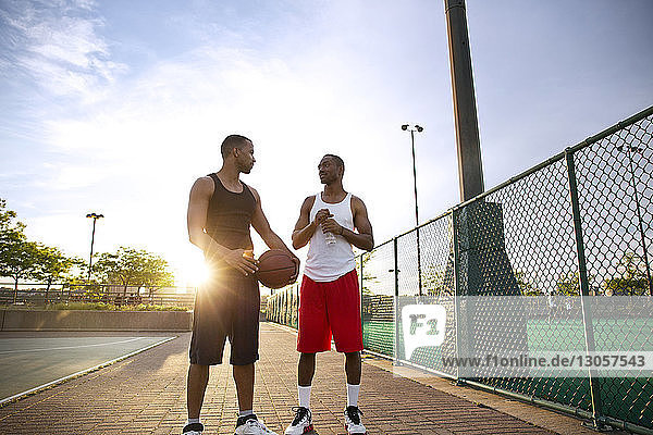 Friends talking while standing in basketball court