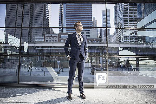 Geschäftsmann mit Händen in den Taschen  der nach oben schaut  während er sich gegen ein modernes Gebäude stellt