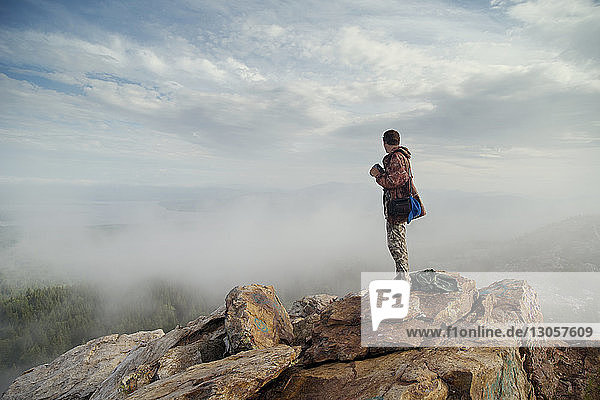 Man standing on rocks against cloudy sky