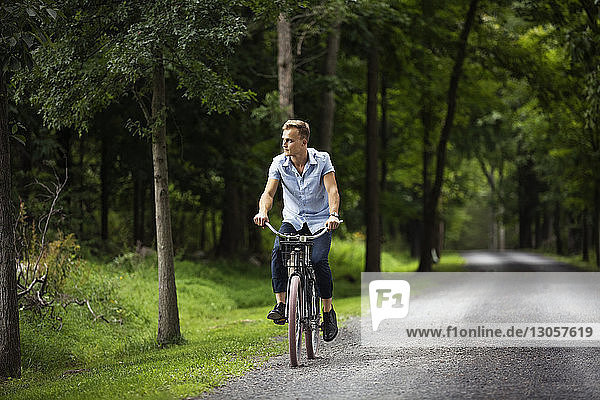 Man looking away while riding bicycle on road
