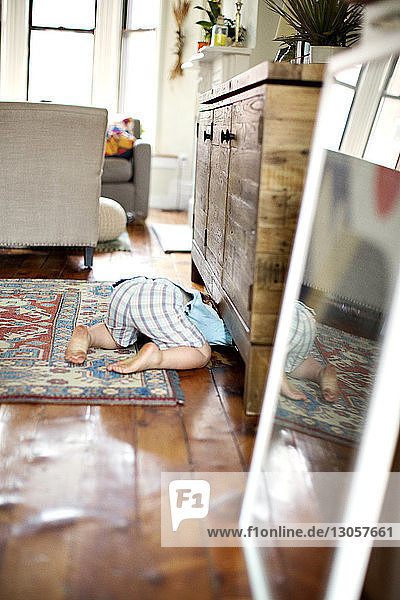 Boy searching under cabinet at home
