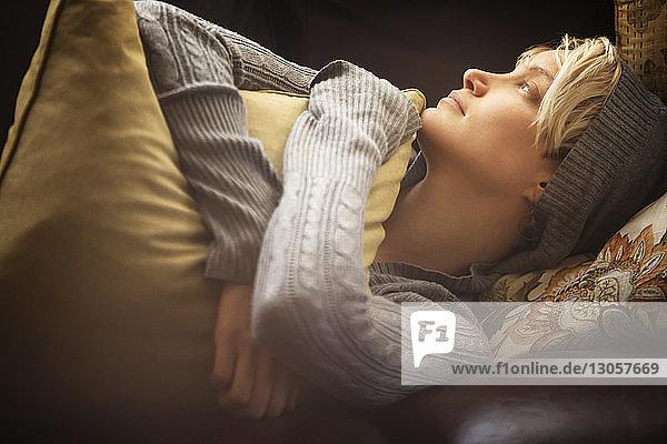 Frau umarmt Kissen  während sie zu Hause auf dem Sofa liegt