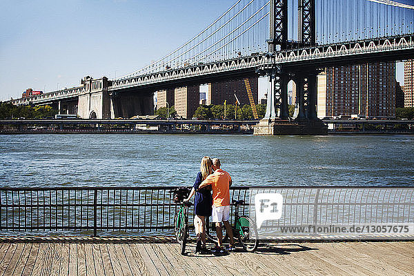 Rear view of couple with bicycles standing against Manhattan Bridge